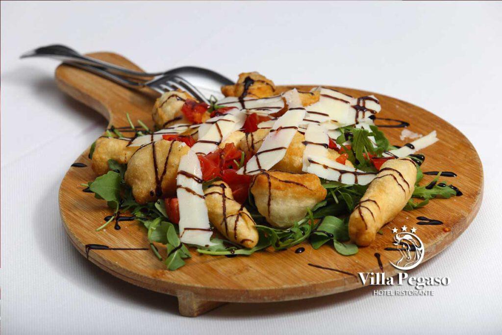 Pizzette fritte con rucola, pomodorini, scaglie di grana e glassa balsamica